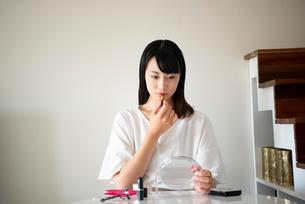 口紅を塗っている女性の写真素材 [FYI03829092]