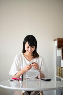 口紅を持って笑っている女性の写真素材 [FYI03829126]