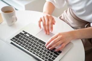 ノートパソコンで作業をしている女性の手元の写真素材 [FYI03829509]