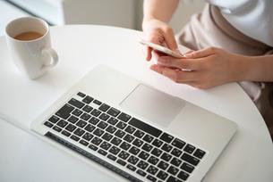 パソコンの前でスマホを触っている女性の手元の写真素材 [FYI03829512]