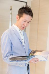 パンフレットを見る男性の写真素材 [FYI03830519]