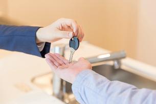 鍵を渡す女性と男性の手の写真素材 [FYI03830528]