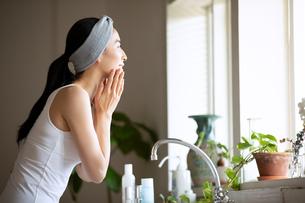 洗顔中に窓の外を見る女性の写真素材 [FYI03830660]