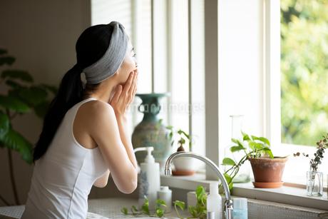 洗顔中に窓の外を見る女性の写真素材 [FYI03830662]
