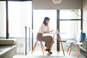 リビングでパソコンを触っている女性の写真素材 [FYI03830679]
