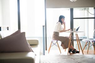 リビングでパソコンを触っている女性の写真素材 [FYI03830680]