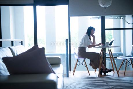 リビングでパソコンを触っている女性の写真素材 [FYI03830681]