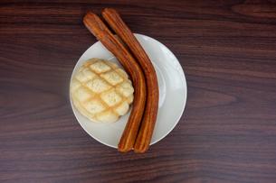 皿の上のメロンパンとチュロスの写真素材 [FYI03830689]