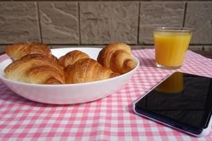 テーブルの上のクロワッサンとオレンジジュースとスマートフォンの写真素材 [FYI03830728]