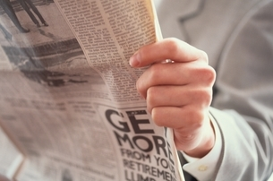英字新聞を読むビジネスマンの手のアップの写真素材 [FYI03831363]