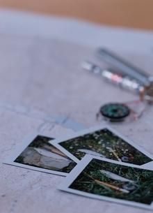 地図の上に置かれた3枚のポラロイド写真の写真素材 [FYI03831626]