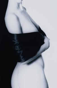 胸を隠してポーズを取る女性の上半身横向きのヌード(B&W)の写真素材 [FYI03832348]