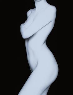 胸を手で隠す女性の横向きのヌード(B&W)の写真素材 [FYI03832359]