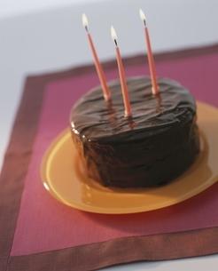 チョコレートケーキにさした3本の赤いキャンドルの写真素材 [FYI03832495]