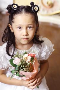 花束を持つ白いドレスのハーフの少女の写真素材 [FYI03833290]