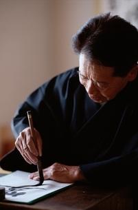 書道を書く日本人老人男性の写真素材 [FYI03833364]