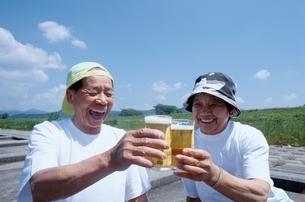 屋外でビールで乾杯する日本人老夫婦の写真素材 [FYI03833368]