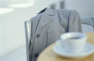 イスに掛けられたジャケットとテーブルの上のコーヒーカップの写真素材 [FYI03833491]