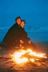 海浜で焚火にあたる2人の外国の女性の写真素材 [FYI03833598]