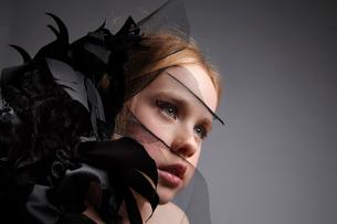 黒い花飾りとブロンド少女の写真素材 [FYI03833617]