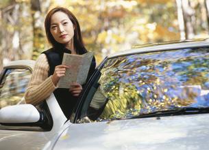 車から降りて地図を見る20代女性の写真素材 [FYI03833915]
