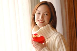 ハート型のプレゼントを持つ女性の写真素材 [FYI03833962]
