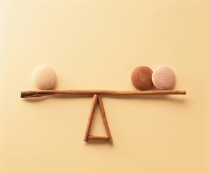 3個の石が置かれた均衡なシーソーのオブジェの写真素材 [FYI03834828]