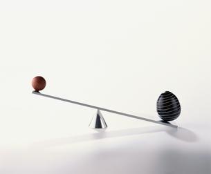 球体が置かれて傾いたシーソーのオブジェの写真素材 [FYI03834829]