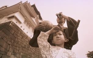 地球儀を持って城の前に立つ侍姿の男性と男の子の写真素材 [FYI03836775]