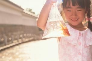 ビニール袋に入った金魚を持った日本人の女の子の写真素材 [FYI03836803]
