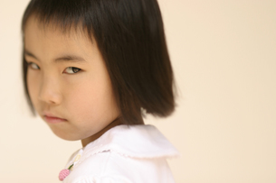 振り向いてにらむ日本人の女の子の写真素材 [FYI03836818]