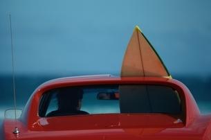 サーフボードを積んだ赤い車の写真素材 [FYI03836842]