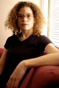 ソファに座るメガネを掛けた外国人女性の写真素材 [FYI03836978]