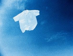 青空に飛ぶ白シャツの写真素材 [FYI03837061]