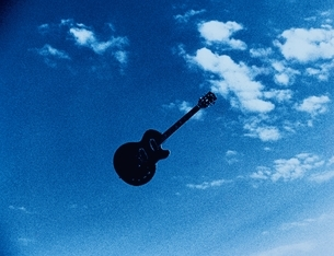 青空を飛ぶギターの写真素材 [FYI03837066]