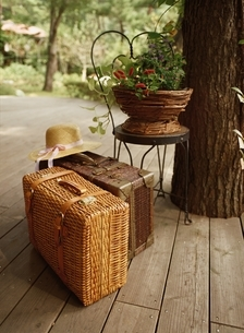籐のトランクケース2つと帽子と椅子の上に鉢植えの写真素材 [FYI03837193]