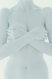 手で胸を覆うヌードの女性の写真素材 [FYI03837317]