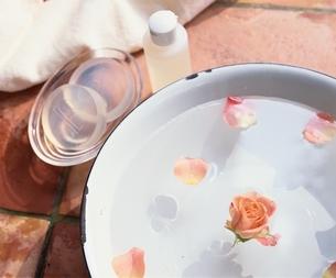 洗面器にの花びらを浮かべたお湯の写真素材 [FYI03838550]