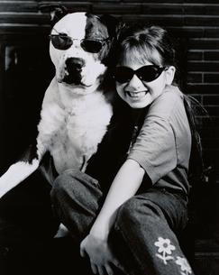 サングラスをかけたイヌと笑顔の外国人の女の子 B/W カナダの写真素材 [FYI03838712]