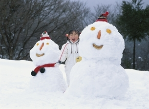 2個の雪だるまと口を開ける日本人の女の子の写真素材 [FYI03839160]