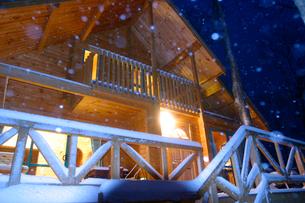 雪と明かりの灯るログハウスの写真素材 [FYI03839395]