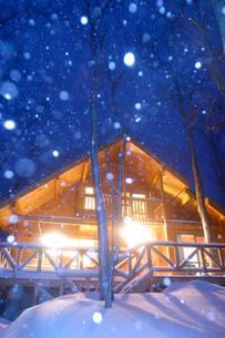 雪と明かりの灯るログハウスの写真素材 [FYI03839397]