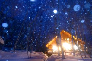 雪と明かりの灯るログハウスの写真素材 [FYI03839398]