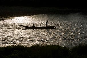 舟で川釣りをする人のシルエットの写真素材 [FYI03839620]