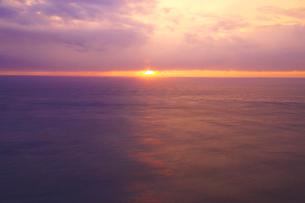 雲間から見える夕日と夕方の海の写真素材 [FYI03839833]