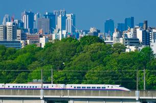 新宿・池袋をバックに東京を走る上越・東北新幹線E2系はやて型の写真素材 [FYI03841503]