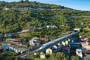 青空に山間部集落の合間を走り抜ける東海道山陽新幹線N700Aの写真素材 [FYI03842677]