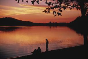 夕焼けの中の2人の釣り人のシルエット コロラド アメリカの写真素材 [FYI03845279]