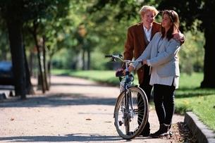 歩道で肩を組む外国人のカップルと自転車 パリ フランスの写真素材 [FYI03848273]