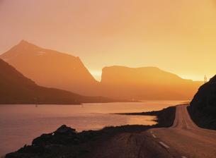 朝焼けに染まる山並みと川辺の道 フィヨルド ノルウェーの写真素材 [FYI03850355]